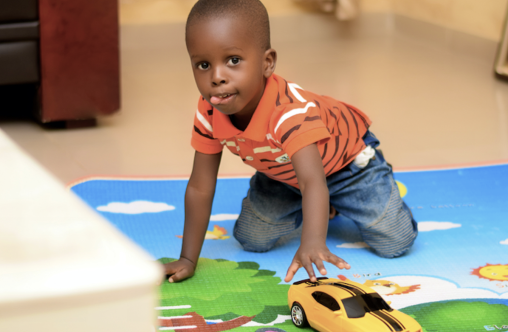 A young boy playing with a toy car